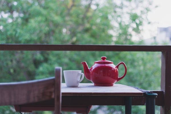 عکس قوری و استکان چای روی میز در طبیعت