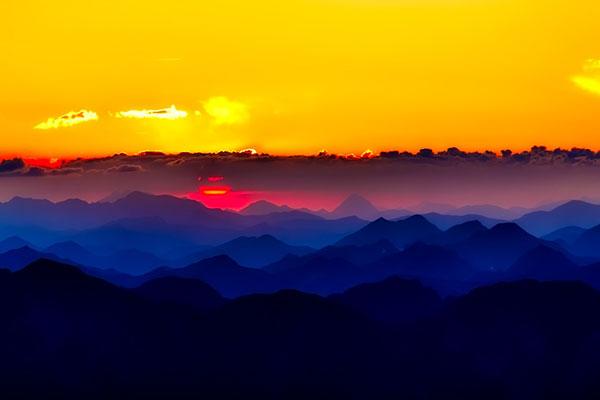عکس طلوع خورشید و کوهستان های آبی