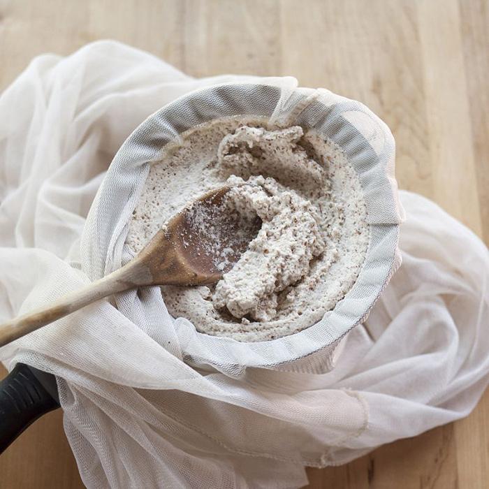 شیر بادام را از صافی رد کنید تا تفاله های آن گرفته شود
