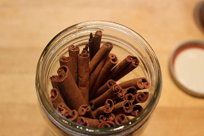 چوب های دارچین را در ظرف شیشه ای بگذارید